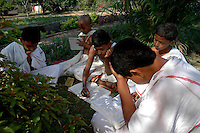 Students of Om Shantidhama studying in the Garden. Om Shantidhama is a residential vedic school for boys. Nestled among the confluence of hills, forest and rivers - Om Shanti Dhama is a world removed from the maddeningly fast and often chaotic urban India. Students from allover the country are selected to take part in its Vedic and free education system. What is unique about this institute is that they have blended the traditional and modern education system. Here computer and science is taught with the same passion as the Vedas and Shastras, helping the students to grow spiritually as well as earn a living. Bonding with the nature and animal world is a mandatory part of the institute's curriculum. Karnataka, India. Arindam Mukherjee