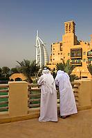 Dubai, United Arab Emirates. Madinat Jumeirah. Burj al Arab Hotel and Mina A'Salam Hotel. Two Arab men enjoying the view from the terrace of the souk/bazaar..