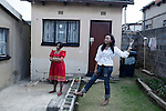 SOWETO, SOUTH AFRICA - MAY 15: Event agency owner Palesa Gcaba stands with her mother outside the house where she grew up on May 15, 2010, in Soweto, South Africa. Palesa is part of the new young generation of black South African's who has obtained a better education and opportunities than their parents. She organizes big events for government departments and private business. Because of being  black and a women, she can tender for government contracts much easier than being a white person. She lives in a posh Johannesburg suburb and drives a late model BMW. Soweto is the largest township in South Africa, located about 10 kilometers southwest of downtown Johannesburg. The population is estimated to be around 2-3 million. (Photo by Per-Anders Pettersson)