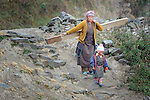 A woman carries a beam for her new house through the village of Gatlang, in the Rasuwa District of Nepal near the country's border with Tibet.<br /> <br /> In the aftermath of the April 2015 earthquake that ravaged Nepal, the ACT Alliance helped people in this village with a variety of services, including shelter and livelihood assistance.