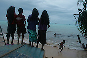 As dusk falls on the third day of 'king tides', 4 young girls from Betio village sing songs and watch the sea water pound their beach, on the South Pacific island of Kiribati.