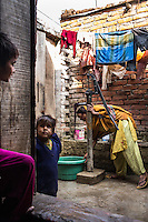 Sultana's mother and sisters go about their house work in their home in Varanasi, Uttar Pradesh, India on 23 November 2013. Sultana was enticed by a trafficker on the pretext of marriage and was raped repeatedly as he filmed her, using the film to blackmail her as he sold her to another trafficker for INR50000 (USD800). Guria has since put almost all of her traffickers into jail, and has provided her with a grant for livelihood support, which she used to start her saree embellishment business.