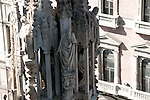 Statues carved on the spires on the roof of the Duomo (Cathedral) in Milan, Italy. One sculpture on a spire of the Duomo in Milan, Italy looks up at the roof.