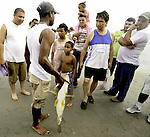 Fisherman in Cartagena, Colombia haggles with locals over the price of his newly caught fish.