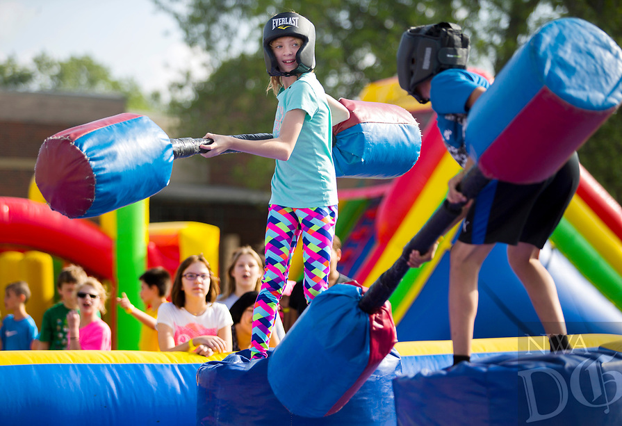 NWA Democrat-Gazette/JASON IVESTER<br /> Nora Schuett (cq) (left) and Edward Lopez, both fifth-graders, try to maintain balance Thursday, May 18, 2017, during the Fun and Field Day at Old High Middle School in Bentonville. Next Friday is the last day of school for Bentonville students.
