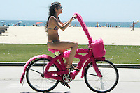 A woman rides an art bicycle covered in fake pink fur along the Santa Monica bike path on Wednesday, August 3, 2011.