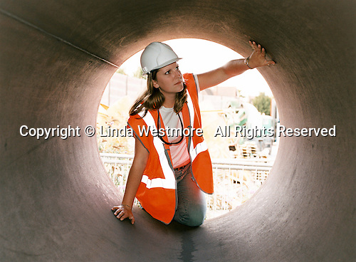 Civil Engineering student on work placementexamines the inside of a large metal pipe.