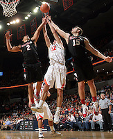 Dec. 22, 2010; Charlottesville, VA, USA; Virginia Cavaliers guard Joe Harris (12) reaches for the rebound with Seattle Redhawks forward Aaron Broussard (2) and Seattle Redhawks forward Chad Rasmussen (15) during the game at the John Paul Jones Arena. Seattle Redhawks won 59-53. Mandatory Credit: Andrew Shurtleff