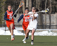 Boston College defender Ali Meagher (9) looks to pass as Syracuse University midfielder Kirkland Locey (8) and Syracuse University midfielder/defender Caz-Marie Norwich (29) close.  Syracuse University (orange) defeated Boston College (white), 17-12, on the Newton Campus Lacrosse Field at Boston College, on March 27, 2013.