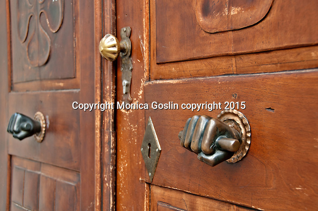 Detail of a door in Merano, Italy with iron decorations of hands holding the bar to open the door