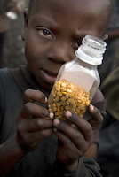 Charles Bade at the Muganga I IDP (Internally Displaced Persons) camp with a small bottle of split peas that he picked from the floor after a food distribution.