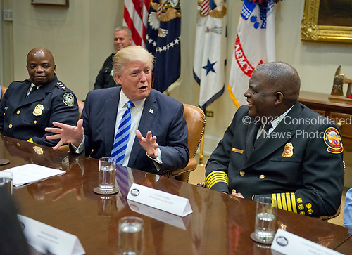 United States President Donald J. Trump meets with the I-85 bridge first responders in the Roosevelt Room of the White House in Washington, DC on Thursday, April 13, 2017. From left to right:  Assistant Chief of Police Rodney Bryant, Atlanta Police Department; President Trump, and Fire Chief Joel Baker, Atlanta Fire Rescue Department.<br /> Credit: Ron Sachs / Pool via CNP