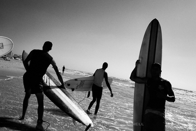 A group of surfers walk along the shore of Sheik Khazdien beach in Gaza City as the swell rolls in from the Mediterranean Sea, Gaza Strip.