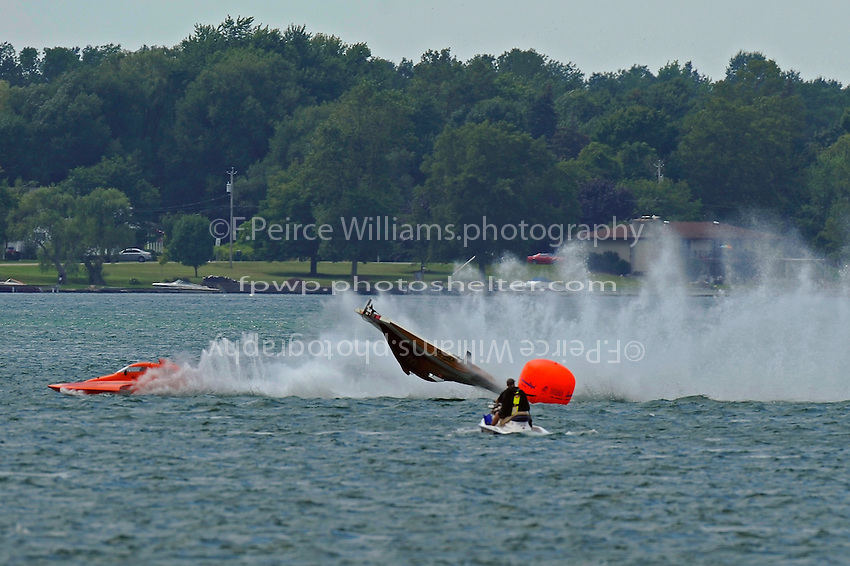 "Frame 11: At the start of the final heat, Kent Henderson, S-00 ""Bank On It""  leads into the first turn when the right side of the boat pulls up and carries the boat into a ""blowover"" flip. The hull spins in the air, comes back to the surface upside down, digs in, and then flips right side up, coming to a rest as CS-79 ""Bad Influence"" races past on the outside. Henderson was uninjured in the accident with slight damage to the boat.  (2.5 Litre Stock hydroplane(s)"