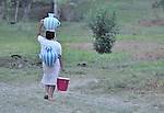 A woman carries water in Victoria 20 de enero, a village of former Guatemalan refugees in Mexico who returned home as a group in 1993, while the country's bloody civil war still raged.
