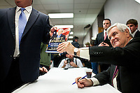Republican presidential candidate Newt Gingrich poses for a picture after signing a copy of his book after addressing the Polk County Republican Party's Robb Kelley Victory Club dinner on Thursday, December 1, 2011 in Johnston, IA.