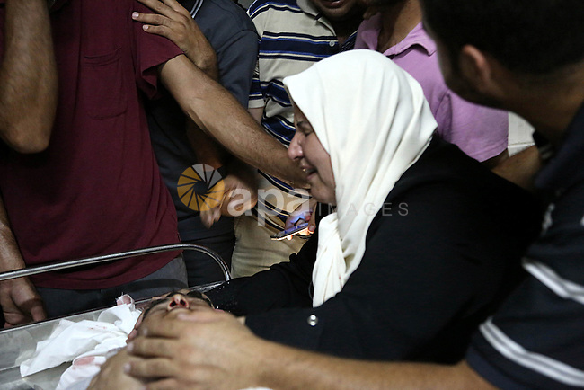 The mother of Mohammed al-Masri, 17, mourns over his body at a hospital morgue, in Beit Lahia in the northern Gaza Strip on July 31, 2015. Al-Masri killed and another wounded after being shot by Israeli gunfire in the northern Gaza Strip Friday near the border fence west of the Beit Lahiya area, a Palestinian medical official said. Photo by Nidal Alwaheidi