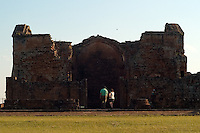 Chilean tourists Domingo Martinez and wife Lucia Medina stand in the entryway of the main church ruins of the Jesuit mission church at Trinidad de Paraná (acute accent on final a), Paraguay. Scores of Jesuit missions in the area where Paraguay, Argentina and Brazil meet were built in the 17th century and abandoned when the Jesuits were expelled in the 18th century. Ruins of some of these missions still haunt hilltops in the region. (Kevin Moloney for the New York Times)