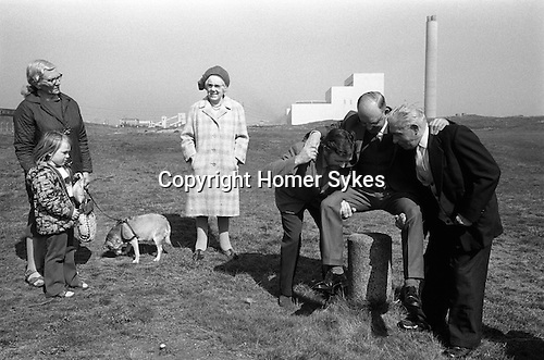 Dunting the Freeholder, Newbiggin by the Sea. Northumberland  1974. Vandalized Moot Stone now use a small concrete pillar. A new freeholder is dunted.<br /> <br /> Lynemouth Power Station in background.