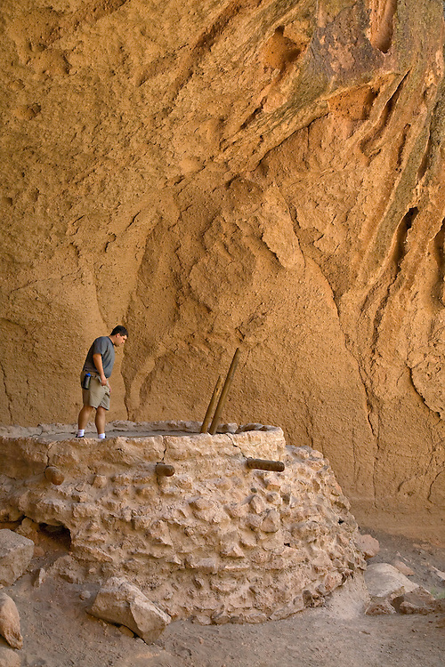 Man looks into reconstructed kiva at Bandelier National Monument, New Mexico