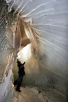 Tourists explore the inside of a glacier. Melting ice water in the summer craetes caves that are possible to access during the winter. The Arctic island of Spitsbergen is the largest of islands in the group that makes up Svalbard. The islands are close to the North Pole and about 60% of the land mass is covered by glaciers. The main activities are mining, tourism and Arctic research. &copy; Fredrik Naumann