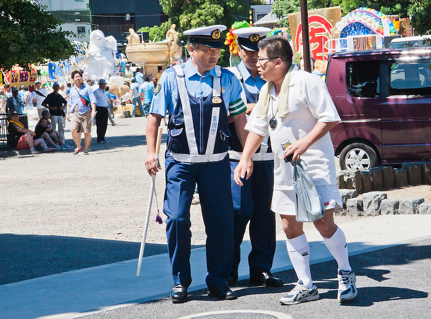 Tokyo Police assist a man who has had too much beer & sunshine