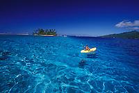 Boy playing in kayak in clear blue waters of Moorea lagoon, motu islet in background