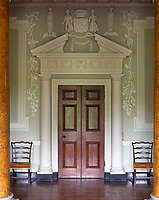 Detail of a mahogany door and a grand pediment in the stuccoed hall of Castle Ward, National Trust