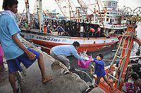 Burmese refugees in Phuket, Thailand. Many of the men spend a day, a week or up to a month out at sea on the precarious fishing boats, earning about $200 a month, while the women work at the port or at home scaling and sorting fish.