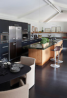 The natural wood kitchen island with its green marble work surface creates a visual impact against the stained black floor and black units in this kitchen/dining room