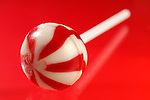 Colorful red white stripy lollipop isolated on red background