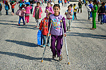 A girl on crutches walks home from school in the Zaatari Refugee Camp, located near Mafraq, Jordan. Opened in July, 2012, the camp holds upwards of 50,000 refugees from the civil war inside Syria. International Orthodox Christian Charities and other members of the ACT Alliance are active in the camp providing essential items and services.