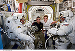 S131-E-009319 (13 April 2010) --- NASA astronauts Clayton Anderson (left) and Rick Mastracchio, both STS-131 mission specialists, attired in their Extravehicular Mobility Unit (EMU) spacesuits; along with astronauts James P. Dutton Jr., pilot; and Dorothy Metcalf-Lindenburger, mission specialist, pose for a photo in the Quest airlock of the International Space Station prior to the start of the mission's third and final spacewalk.