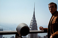 """Manhattan, New York City - May 1969. Picture of Yves Montand taken on top of the Pan Am building. Yves Montand is playing a role on top of the building for the film """"On a Clear Day You Can See Forever"""" directed by Vincent Minnelli and co-starring Barbara Streisand. Yves Montand (October 13, 1921 - November 9, 1991) was an Italian-born French actor and singer, who was discovered by renown singer ´Edith Piaf, and is most known for his performance in the movie Jean de Florette."""