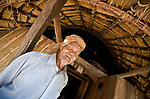 Old man at entrance to traditional Manggarai home, Wae Rebo village, Flores.