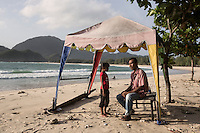 """Indonesia – Sumatra – Aceh – Lampuuk – Sabri Rahman, 34 years old sits under the shade of a small gazebo with his daughter on the beach where he owns a bar.  Sabri was on the porch of his house when the wave carried him several km away. Hours later when the water receded and Rahman came back to a scene of utter devastation, he started to frantically look for his family. The then 24-year-old guy volunteered to gather, pile up and bury hundreds of bodies, but was not able to find any member of his family, because most of the bodies had been pushed km away. Rahman lost 22 relatives, including his parents and six of his siblings. His 9-year-old brother was the only other survivor. """"It was extremely difficult to deal with my feelings"""" he explains. Although his kids helped him deal with the pain, """" I still have to keep myself busy in order not to think about it"""" he says, fondly caressing his daughter Sasqia."""