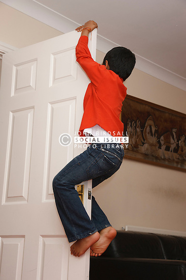 Boy climbing up door in living room.