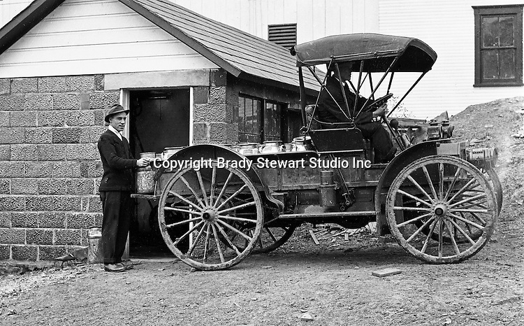 Southwestern Ohio:  Farm worker loading milk containers onto the International Harvester Auto Wagon at the Brady Family farm - 1916