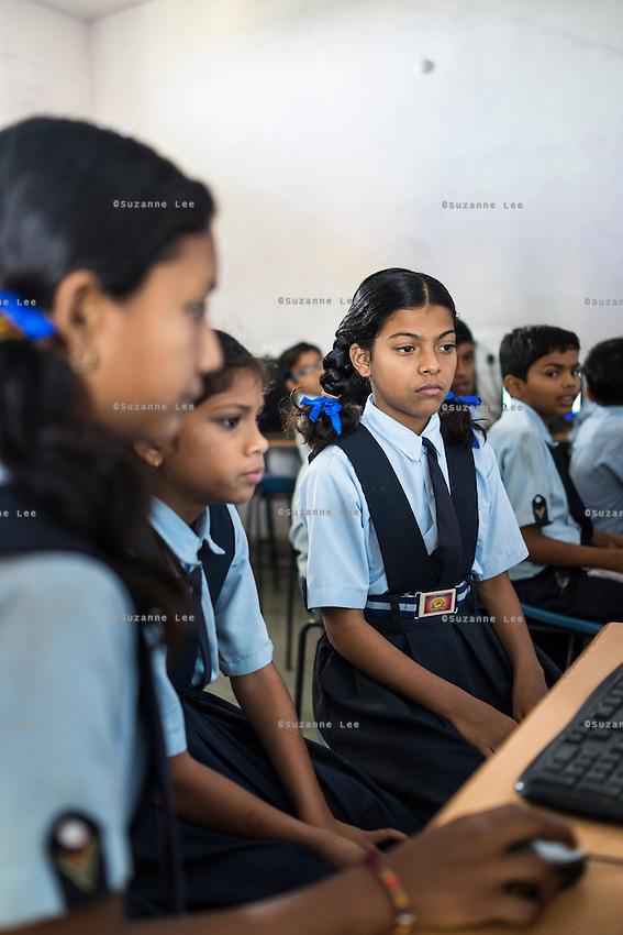 Three female students (L-R: Mayuri Rathore, 12; Antim Sharma, 11; and Shivani Patidar, 11) share a computer during the Computer Class in Vasudha Vidya Vihar school in Khargone, Madhya Pradesh, India on 12 November 2014. The school was built using the Fairtrade Premium of the Fairtrade Cotton Producers. Photo by Suzanne Lee for Fairtrade