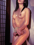 Beautiful naked asian woman standing at a wall with tied hands. Bondage Shibari art nude photo.