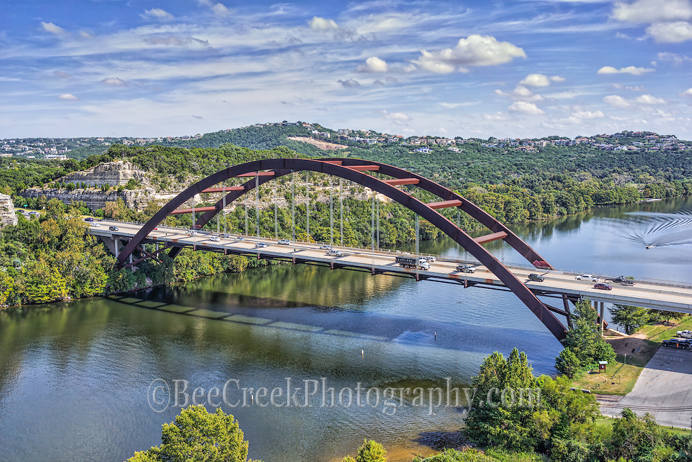 A little different aerial view of the Austin 360 Bridge view over Lake Austin.  This was an aerial capture of the Pennybacker Bridge as we were doing a job for a client in this area so we had permission to photograph from here.  Great day with nice blue sky and good clouds.  Only one lone boat on the water so you can see the reflections in the waterbeecreekphoto.com, Tod Grubbs,