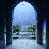 Arches lead out to the traditional open-air central courtyard where an ornately tiled pool is surrounded by lemon trees