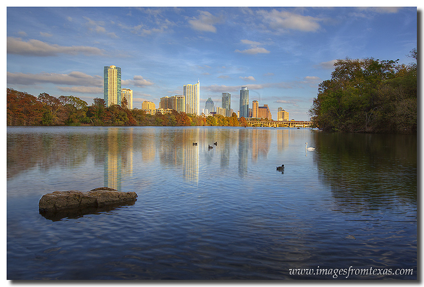 From Lou Neff Point on a late November afternoon, the cool waters of Lady Bird Lake offer a nice reflection of the Austin skyline and the Autumn colors that surround Zilker Park. Prominent in the Austin image are the tallest building, the Austonian, and the iconic Frost Bank Tower.