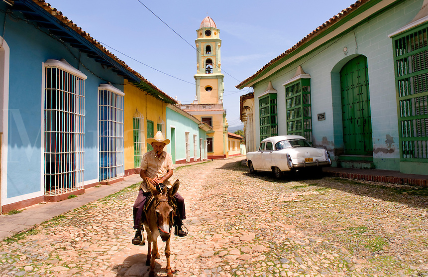 Old man riding donkey on cobblestone scene with old car in street scene with old church of the old colonial city of Trinidad in Cuba