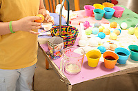 Photo of a family craft table all set up with cups and different colored dye for coloring Easter Eggs.