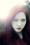 Close up of a girl with red hair and light behind her looking at the camera.