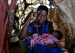 A woman and her baby sit in their small shelter in the Dadaab refugee camp in northeastern Kenya. Tens of thousands of refugees have fled drought-stricken Somalia in recent weeks, swelling what was already the world's largest refugee settlement.