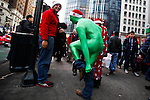 A man change his customes at the street while people dress in merry Christmas characters take part at the Santacon's Annual Festival at Manhattan in New York, United States. 14/12/2012. Photo by ZAMEK