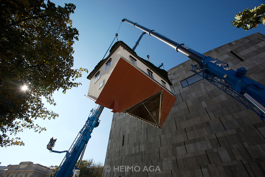 "MUMOK (Museum Moderner Kunst), Vienna. Exhibition of Austrian artist Erwin Wurm. ""His most recent prominent work, visible from afar, is the object ?House Attack?, installed on MUMOK's external façade: the single family house as a symbol of the everyday, privacy, as well as small-mindedness explodes like a bomb into the façade of the museum ? the institutionalized museum temple. In its visual presence ?House Attack? represents an ambivalent metaphorics exemplary for the current work of the artist, a focus of the exhibition."""