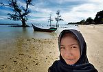Ten-year old Fathan Nur Selani walks on the beach at Lhok Me, in Indonesia's Aceh province. The girl's mother sells coconuts and soft drinks to tourists on the beach. The 2004 tsunami struck the coastal village when Fathan was just three weeks old. YEU, a member of the ACT Alliance, worked with the village to build new houses in a safer area, as well as help revitalize their income generating activities, including Fathan's mother's small business. The tsunami killed 221,000 people in Aceh province and left more than 500,000 displaced.<br /> <br /> Parental consent obtained.
